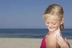 Рука прикладывая солнцезащитный крем к девушке на пляже стоковые изображения rf