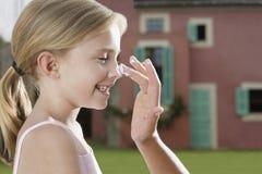 Рука прикладывая солнцезащитный крем к носу девушки стоковое изображение