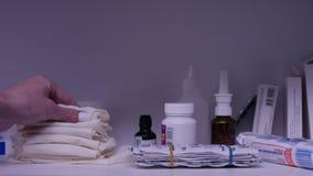 Рука принимает полотенце от полки с медицинами Бутылки пилюлек медицины аранжировали на полке на аптеке Удерживание руки Стоковые Фотографии RF