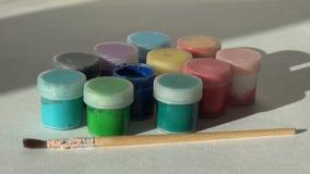 Рука принимает, раскрывает и кладет краску гуаши опарника голубую акриловую Homew сток-видео