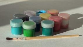 Рука принимает, раскрывает и кладет краску гуаши опарника голубую акриловую Homew видеоматериал