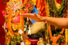Рука принимая жару пламени как благословение от освещенной лампы глины na górze diwali Индии durgapuja идола стойки или поклонени Стоковое Изображение