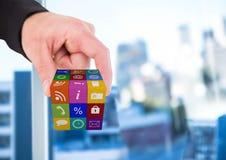 рука принимая куб значков применения Запачканная предпосылка офиса Стоковая Фотография RF