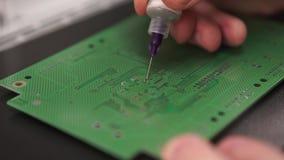 Рука при инструмент ремонтируя сотовый телефон и другие устройства Фабрика продукции микросхемы Технологический процесс собирая акции видеоматериалы