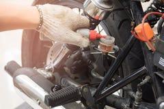 Рука проверки механика и добавляет рабочую жидкость для гидравлического тормоза к мотоциклу, selec Стоковые Изображения