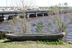 Рука произвела каное сидя на банках реки Стоковая Фотография
