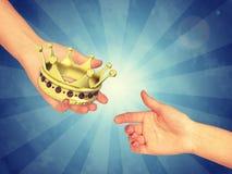 Рука проходя крону золота стоковое фото rf
