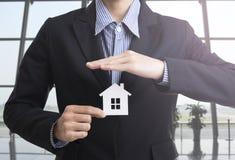 Рука продавца дела держа страхование жилья Стоковые Изображения