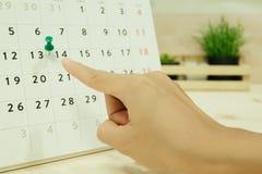 Рука пункта женщины к дню 14 на carlendar помещенном на деревянном tabl Стоковое Фото