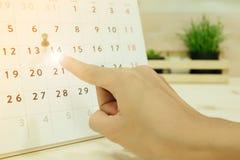 Рука пункта женщины к дню 14 на carlendar помещенном на деревянном tabl стоковая фотография