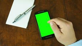 Рука работая на экране зеленого цвета стола smartphone акции видеоматериалы