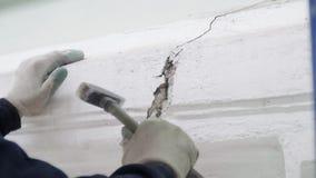 Рука работника в белых перчатках использует небольшой молоток для ударять часть стены фасада видеоматериал