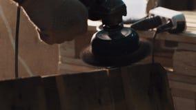 Рука работника в машине точильщика пользы перчатки для того чтобы приглаживать деревянный паллет окаймляется видеоматериал