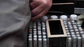 Рука работника кладет цилиндрические металлические штыри в деревянную коробку с круглыми отверстиями сток-видео