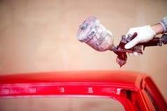 Рука работника крася клобук автомобиля в автоматической мастерской Стоковое Изображение