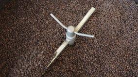 Рука работника позволила процессу старта работая смешивать зажаренные зерна кофе в фабрике акции видеоматериалы