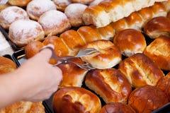 Рука работника хлебопекарни выбирая вверх хлеб с схватом Стоковые Фото