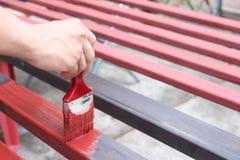 Рука работника человека держа paintbrush покрашенный стальным для indu стоковое изображение