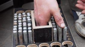 Рука работника человека кладет цилиндрические металлические штыри в деревянную коробку с круглыми отверстиями сток-видео