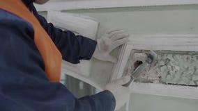 Рука рабочий-строителя держит небольшой молоток и ударяет крошечную часть стены фасада акции видеоматериалы