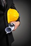 рука рабочий-строителя держа документы и шлем проекта Стоковая Фотография RF