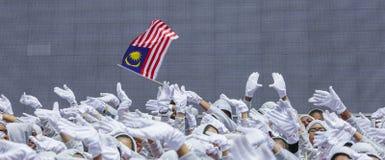 Рука развевая флаг Малайзии также известный как Jalur Gemilang стоковое фото rf