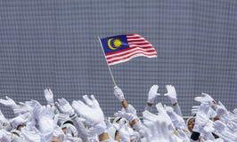 Рука развевая флаг Малайзии также известный как Jalur Gemilang стоковое изображение rf