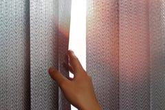 Рука раскрывает черные вертикальные шторки ткани на окне конец вверх стоковые изображения
