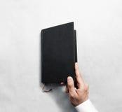 Рука раскрывая пустой черный шаблон модель-макета обложки книги Стоковые Фотографии RF