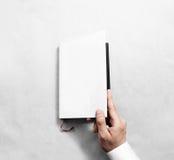Рука раскрывая пустой шаблон модель-макета крышки белой книги Стоковые Изображения