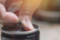 Рука раскрывая чонсервную банку утюга Смогите с питьем колы стоковые изображения