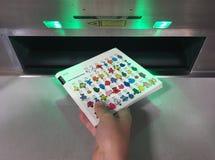 Рука ребенка возвращающ книгу в автоматизированную машину возвращения книги стоковое изображение rf