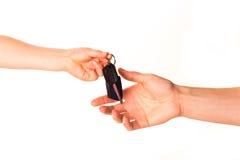 Рука ребенка держа ключ автомобиля и вручая его сверх Стоковые Фотографии RF