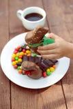Рука ребенка держа большой зайчика шоколада над плитой Стоковые Фото
