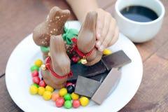 Рука ребенка держа большой зайчика шоколада с колоколом Стоковые Изображения RF