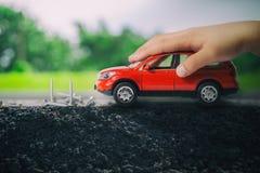 Рука ребенка играя красный автомобиль там препятствия преграждая фронт автомобиля как группа в составе винты Стоковые Изображения