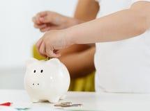 Рука ребенка кладя деньги штыря чеканит в белый шлиц piggybank Стоковая Фотография RF