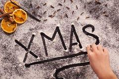 Рука ребенка писать xmas в распространении муки на таблице стоковое фото