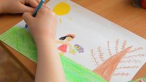 Рука ребенка рисует с красочными карандашами Чертеж рисовал, дети учит о мире, домах притяжки, деревьях, солнце видеоматериал