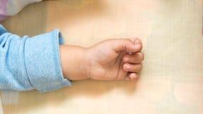 рука ребёнка кладя на кровать Стоковое Изображение