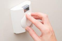 Рука регулируя комнатную температуру с термостатом установленным стеной стоковое изображение rf