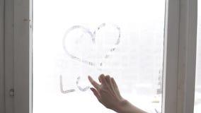 Рука рисует сердце влюбленности на холодной fogged предпосылке окна, изображении крупного плана акции видеоматериалы