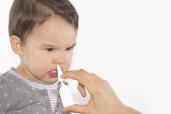 Рука родителя больной маленькой девочки прикладывает носовой брызг Стоковое Изображение