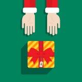Рука Санта Клауса дает подарок с Рождеством Христовым Стоковые Изображения RF