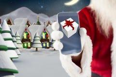 Рука Санта Клауса показывая подарок рождества на экране мобильного телефона Стоковое фото RF