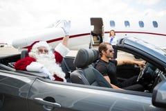 Рука Санты развевая пока водитель управляя автомобилем с откидным верхом Стоковое Изображение RF