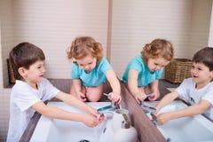 Рука сестры и брата моя в ванной комнате Стоковое Фото