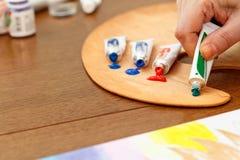 Рука сжимая краску от трубки Стоковые Изображения