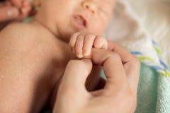 Рука спать младенца в руке конца матери вверх, новый fa Стоковые Фото
