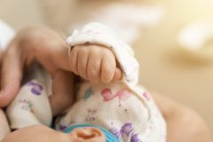 Рука спать младенца в руке матери пока кормящ грудью Стоковое фото RF